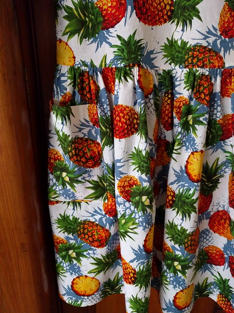 A close up of a pineapple print dress.