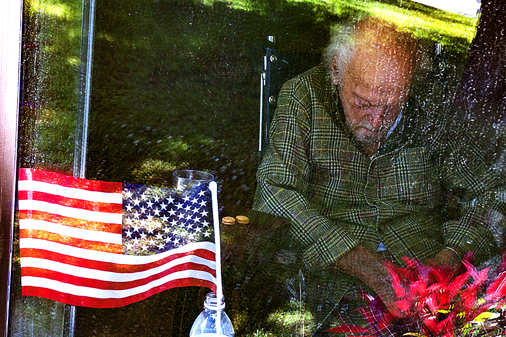 Man-in-wheelchair-in-nursing-home-with-flag--Sunnyvale