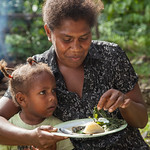 A mother and her daughter share a meal of Mozambique tilapia, cabbage and potato cooked with coconut milk, Taflankwasa village, Malaita Province, Solomon Islands. Photo by Filip Milovac.