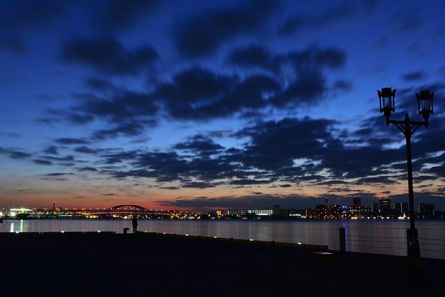 ハーバーランドから見る夜明けの写真。釣り人が釣りをしている。