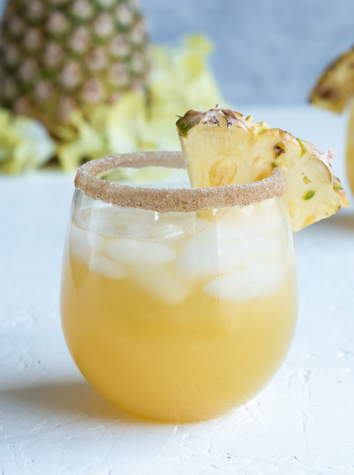 single glass of Spiced Pineapple Rum Punch with cinnamon sugar rim and pineapple wedge
