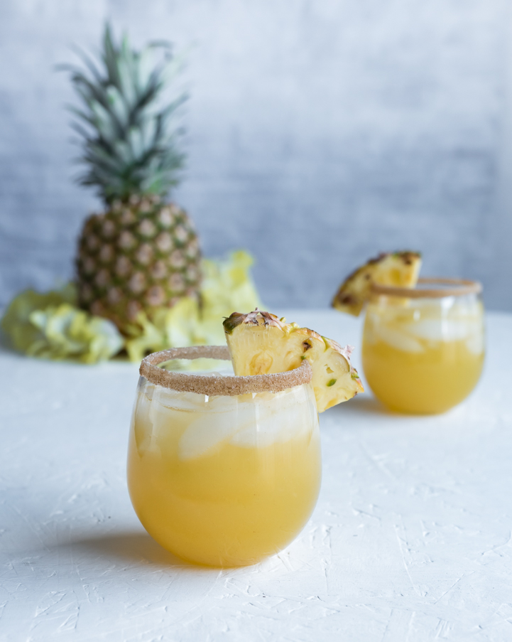 two cocktail glasses filled with rum punch, pineapple wedges, whole pineapple, yellow flower lei
