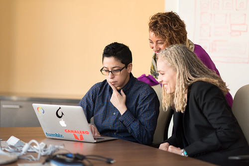 three women of varying races and gender expressions contemplate a laptop screen