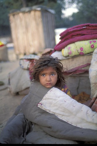 A young child wrapped in blankets to stay warm | by World Bank Photo Collection