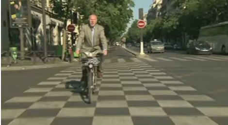 Eric Britton in a checkerboard crosswalk in Paris (still from the Pedal Power documentary)