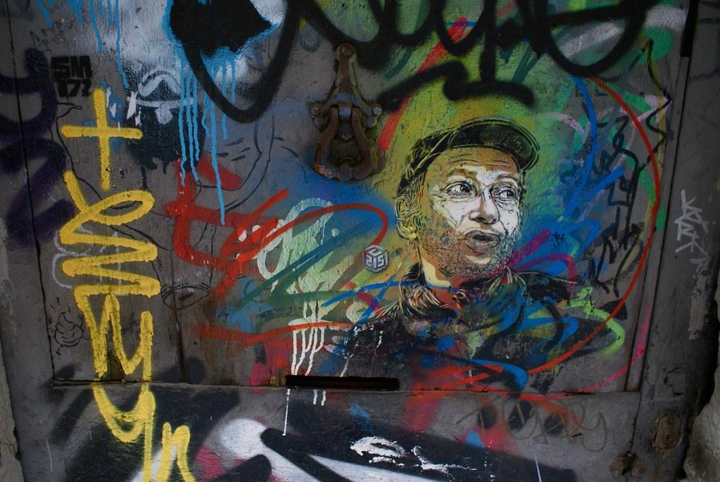 Pochoir et portrait sur une porte de Barcelone.