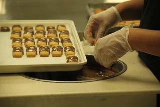 Dunking the shortbread in chocolate at the Big Island Candy Company | by @harryshuldman