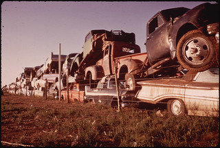 Junked Automobiles Are Piled Three Deep Along Fence | by The U.S. National Archives