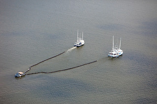 Three boats try to skim off spilled oil. | by Kris Krug