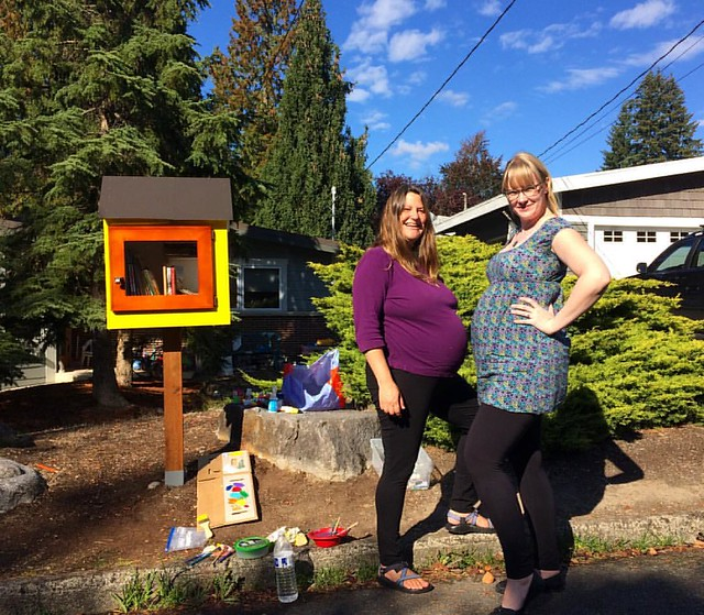 A couple of pregnant ladies enjoying a sunny Fall day.