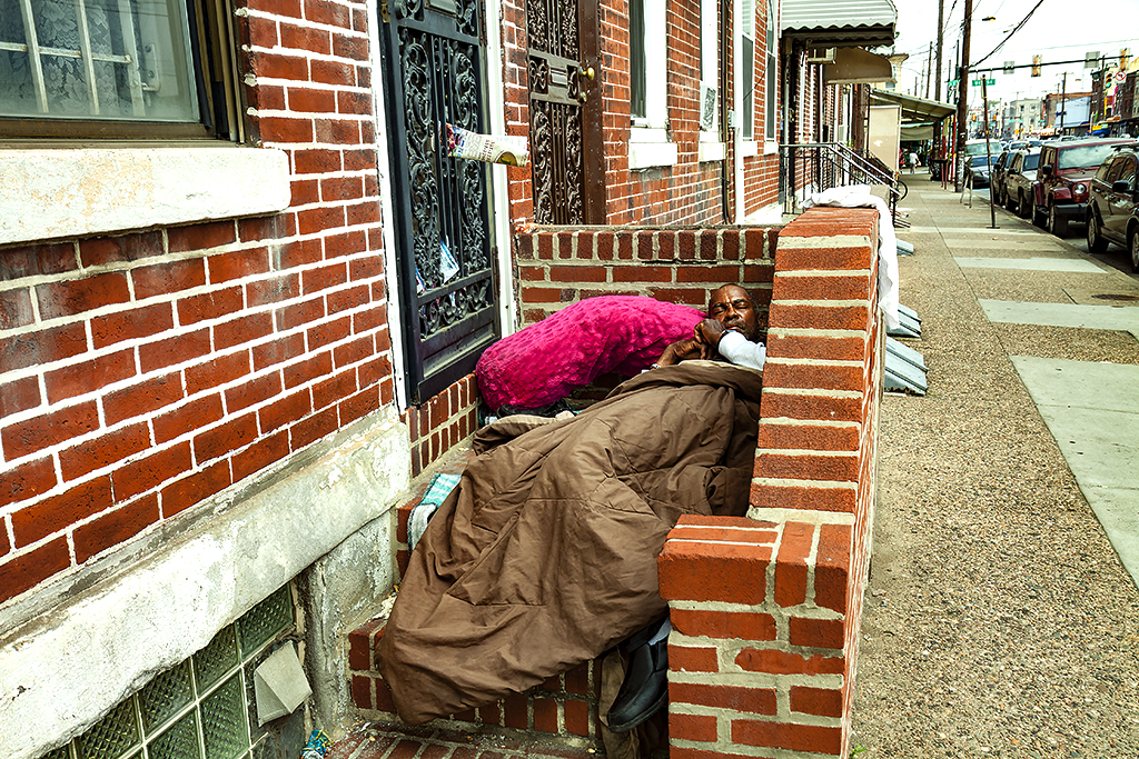 Man-sleeping-at-top-of-steps-in-front-of-house-on-Washington-Avenue--Italian-Market
