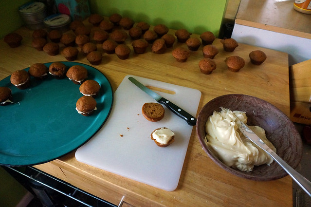 Assembly station: A pile of mini-muffins at the back of the counter, a partially filled platter to the side, and in the middle a cutting board, a small serrated knife, and a bowl of cream cheese frosting ready for slathering
