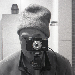 reflected self-portrait with Smena 1 camera and grey hat (square crop)