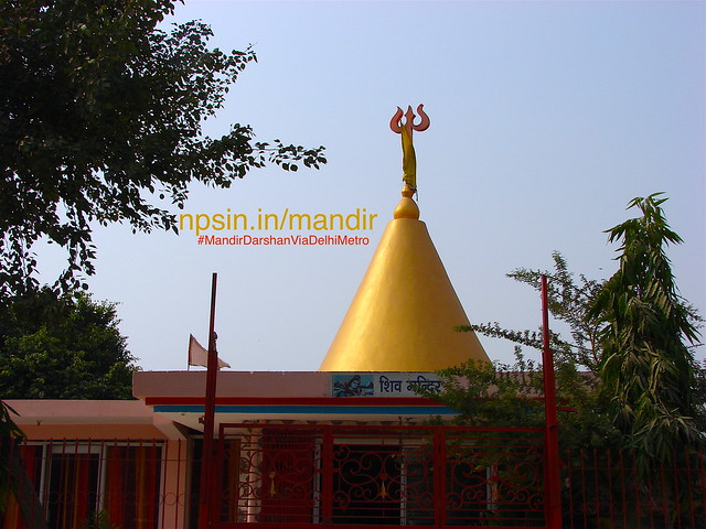 Golden shikhar having Lord Shiva Trishul with Canal side entry gate with Green Area.