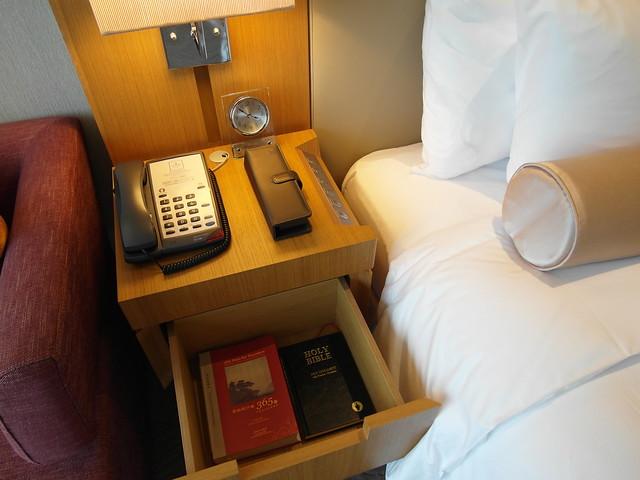 床頭旁邊有電視遙控器、電話、聖經@台中日月千禧酒店