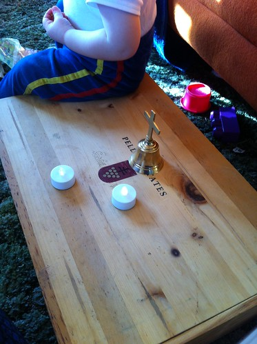 The wooden box with two lit LED tea lights and the brass bell set up on top.