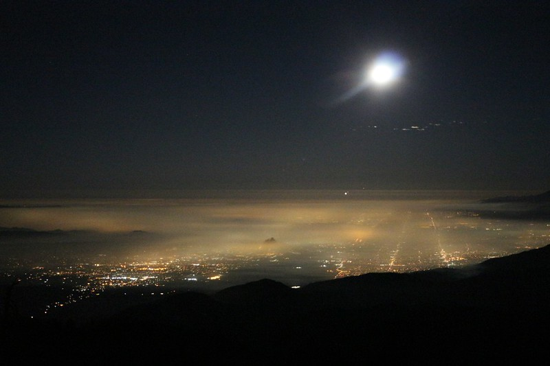 The lights of Los Angeles at night shining up through the haze under a full moon from the Limber Pine Bench campground