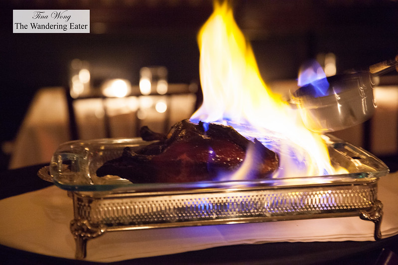 Pouring the flambéed liquor onto the roast duck