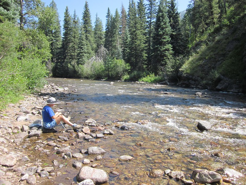 Vicki filtering water from the Pine River where we stopped for lunch and had a nap
