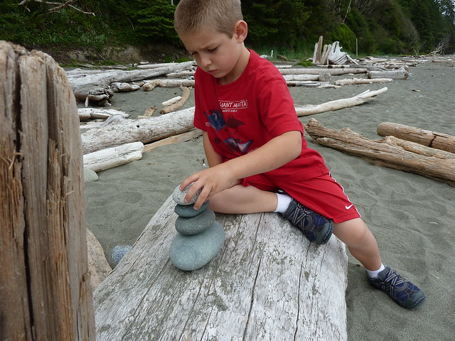 a boy stacks stones on a beach