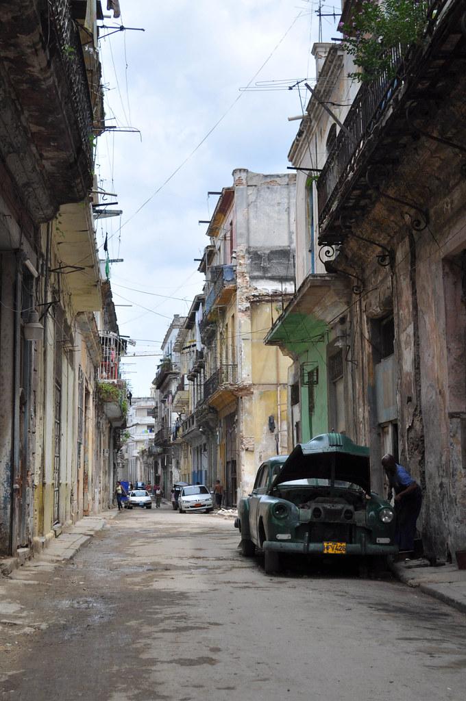 A man working on a car streetside in Havana, Cuba