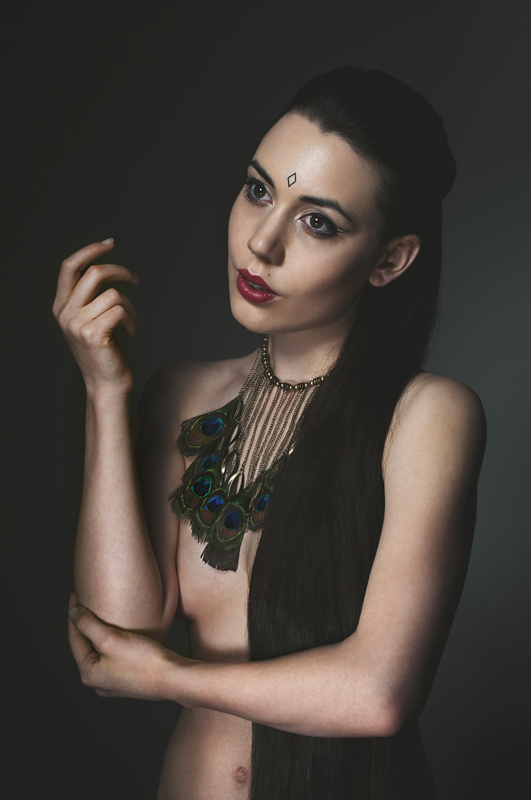 Gestalta photographed by Adam Rowney. Golden, painterly portrait of a girl with peacock feather necklace