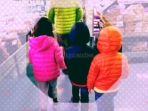 In winter wear and following dad around in the supermarket, doing some grocery shopping.