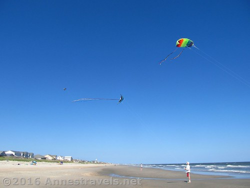 The three best-flying kites - a parastunt, a delta stunt, and a box kite that lazily spins as it flies. On Holden Beach, North Carolina