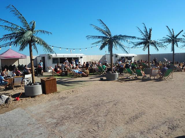 hernesaarenrantaP8070655,hernesaarenrantaP8140896, hernesaari, hernesaarenranta, kokemukset, arvio, kesä, summer, finland, helsinki, miten päästä, visit helsinki, visit finland, helsinki tips, kesäpäivä, hot summer days, helsinki riviera, palmut, palm trees, sand, hiekka, meri, sea, rantatuolit, sunbathing chairs, food and drinks,