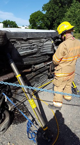 photos of firefighters stabilizing an overturned vehicle