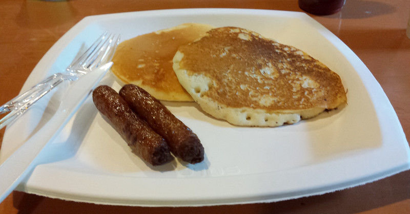 recyclable plate with plastic silverware, two sausages, and two pancakes