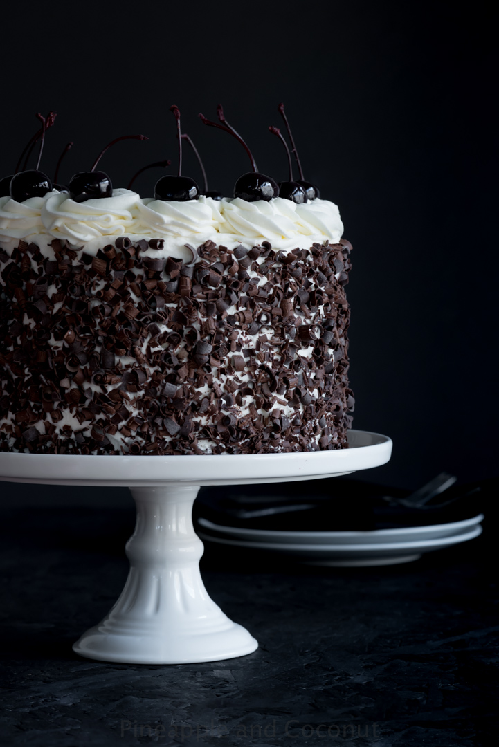 ayer cake covered in chocolate curls on a white cake stand, decorated with whipped cream and dark cherries