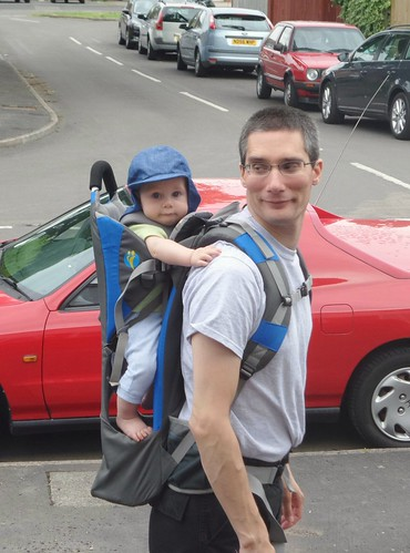 a man looking over his shoulder at a baby in his backpack