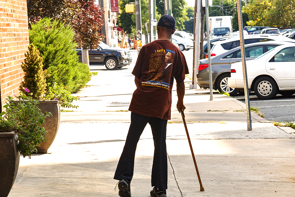 Man with cane wearing Martin Luter King T-shirt--Bella Vista