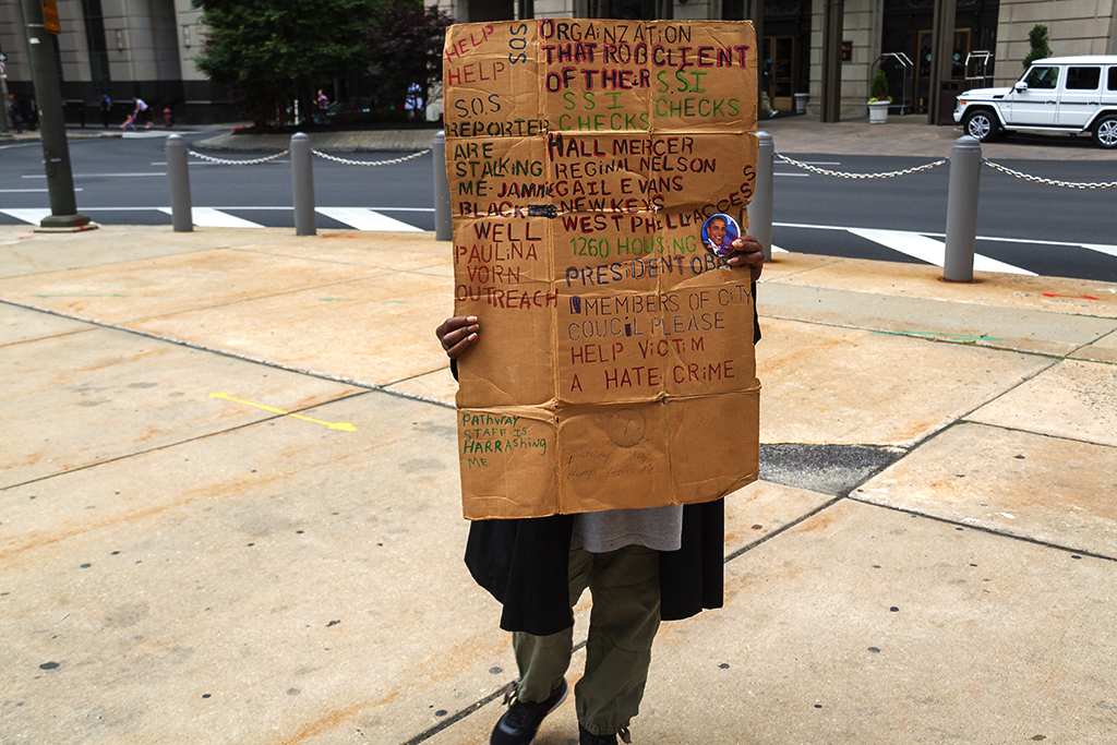 Woman with confusing sign protesting outside City Hall--Center City
