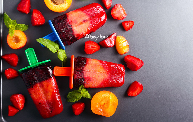 Berry and fruit ice cream pops on black surface
