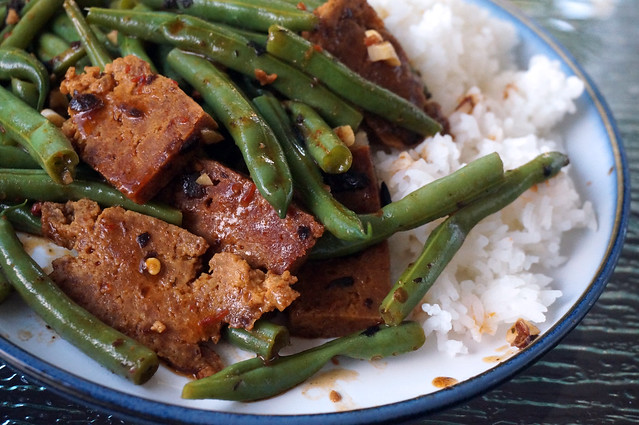Green beans and seitan in black bean sauce: zoomed in to show a sheen of oil glistening on the beans, small bits of garlic, chili seeds, and black beans sticking to the rough fried crust of the seitan.