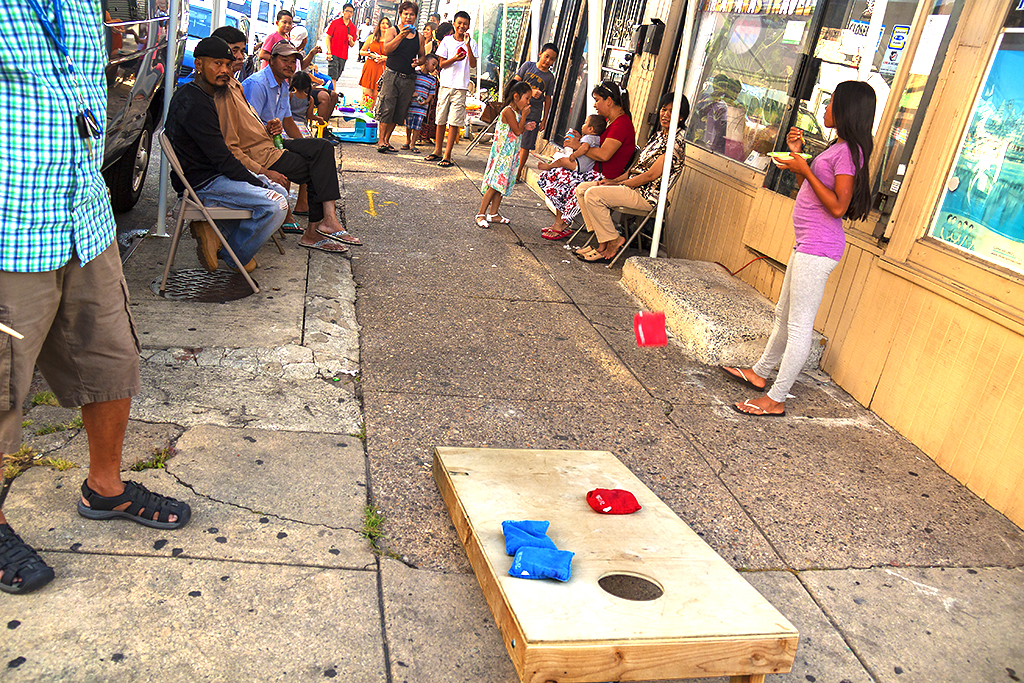 Cornhole game on sidewalk--Little Cambodia