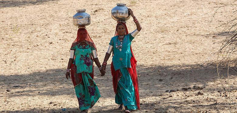 Indian women in rural drylands walking to get water.