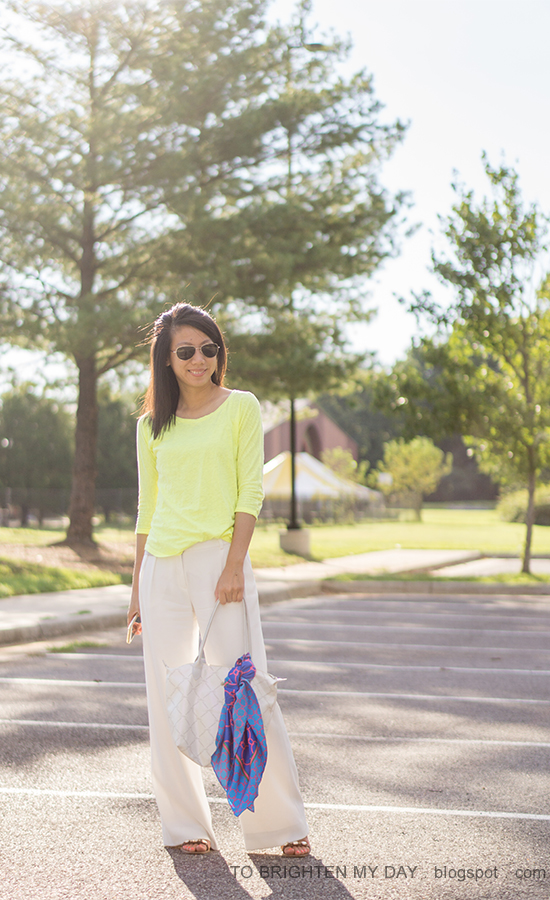 neon yellow top, white wide-legged pants, white tote with bright blue scarf