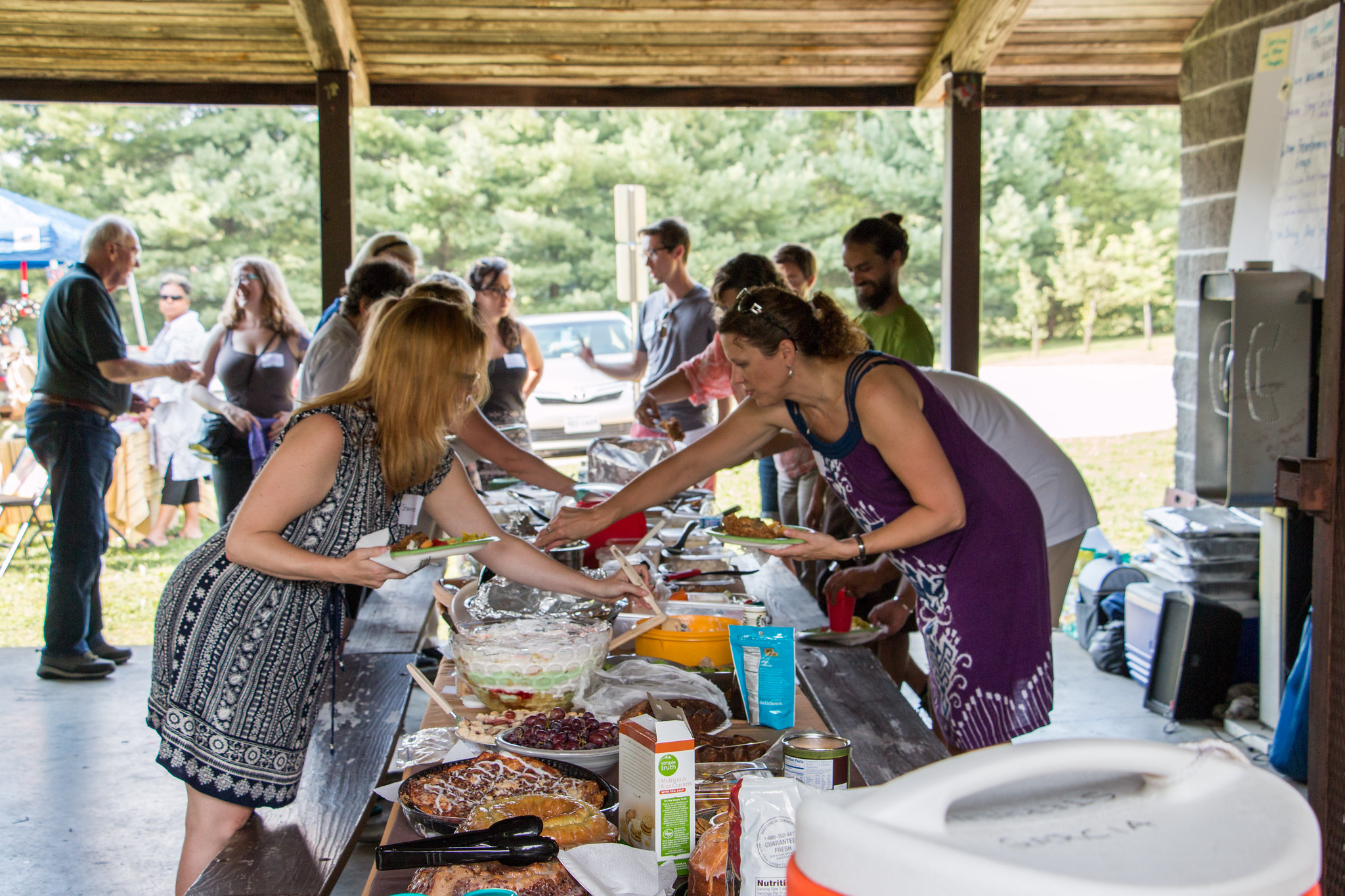 Photo of people grabbing food from a picnic table covered with different dishes.