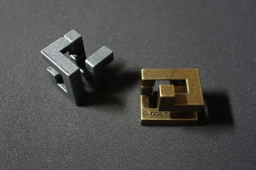 "HUZZLE_CAST COIL_(2016_10_01)_1_resized_1 ""Huzzle"" という知恵の輪的な立体パズルの写真。2個の金属製の角ばった複雑な立体形状が置かれている。向かって右側は黄金色で左側は銀色である。"