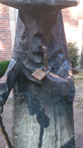 """Figur """"Heidemann"""" auf dem Pantaleonplatz Roxel mit Vorhängeschloss"""