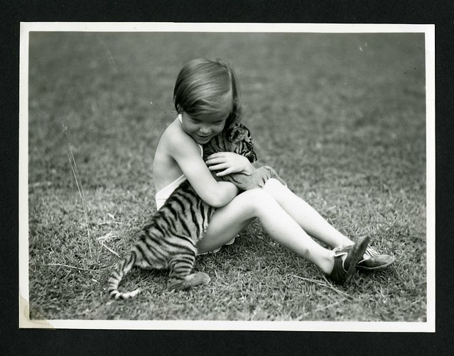 Unidentified child with tiger cub photographed during the the National Geographic Society-Smithsonian Institution Expedition to the Dutch East Indies, 1937