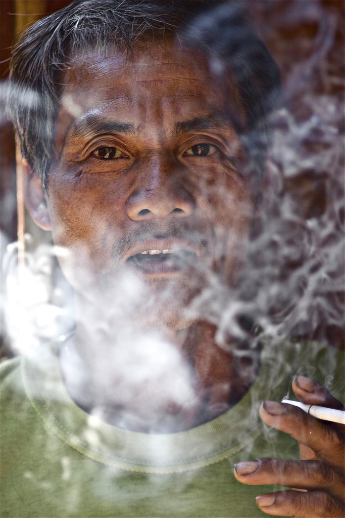A Hmong Gentleman Puffs On His Cigarette