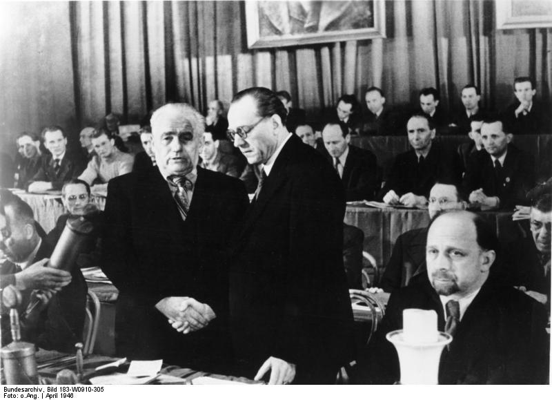 Apretón de manos entre Wilhelm Pieck (izquierda) y Otto Grotewohl durante el congreso donde se formó el SED en abril de 1946. Foto de Abraham Pisarek (Bild 183-W0910-305)