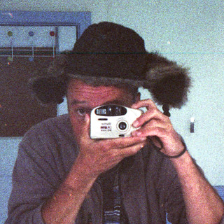 refelcted self-portrait with Vivitar EZ Big View camera and dishevelled hat (square crop)