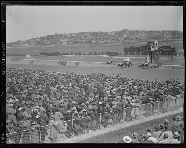 Crowd watches as the winner crosses the finish line at Suffolk Downs