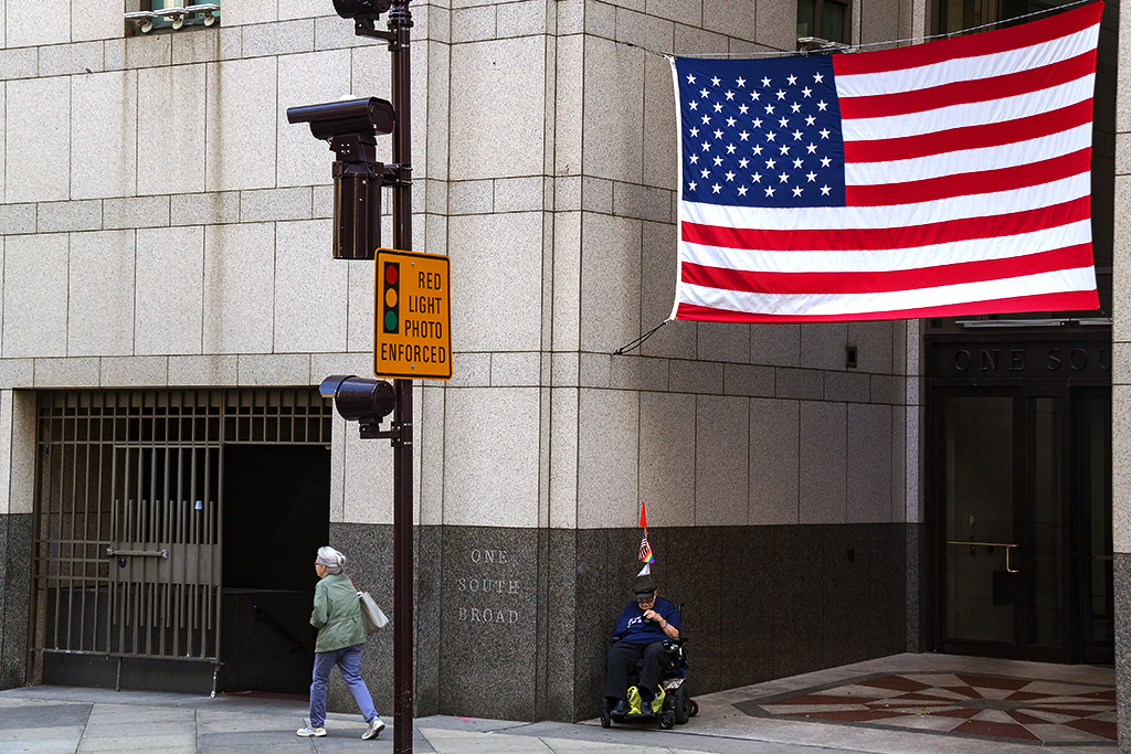 Woman in wheelchair beneath large flag--Center City