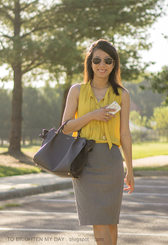 mustard yellow pleated top, gold pendant, gray pencil skirt, gray tote